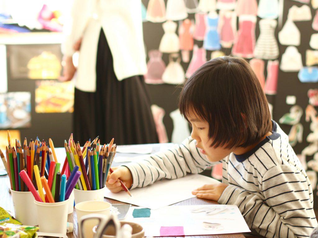 デザイン教室 でデザインイラスト画を描く子ども