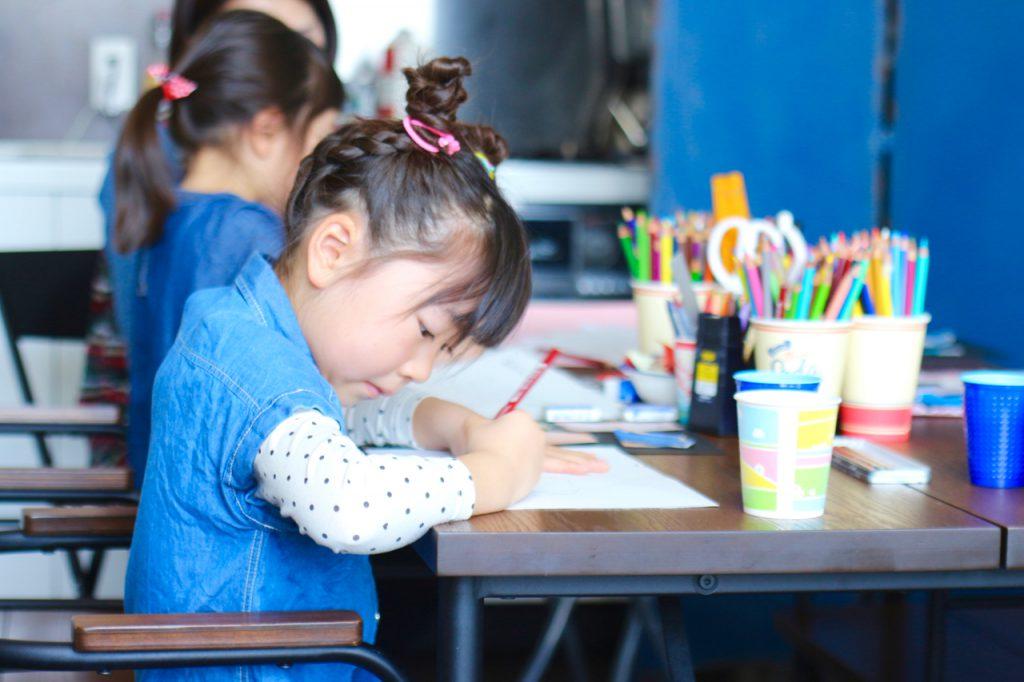 教室にてファッションデザインを考える子供